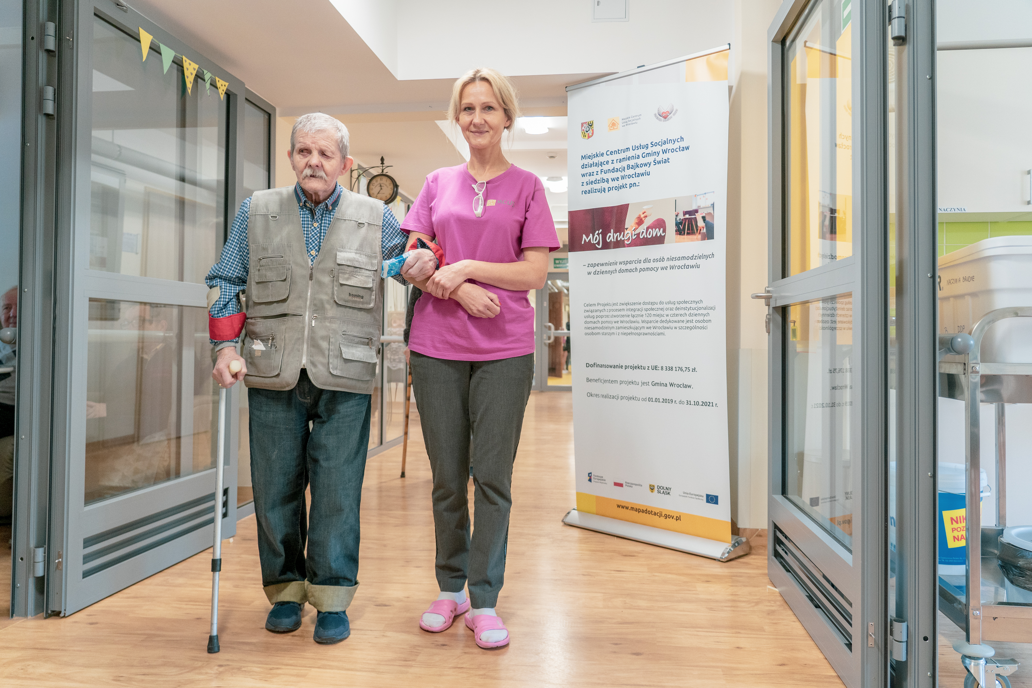 An elderly man walking along the corridor with a nurse in a social welfare home in Wroclaw.