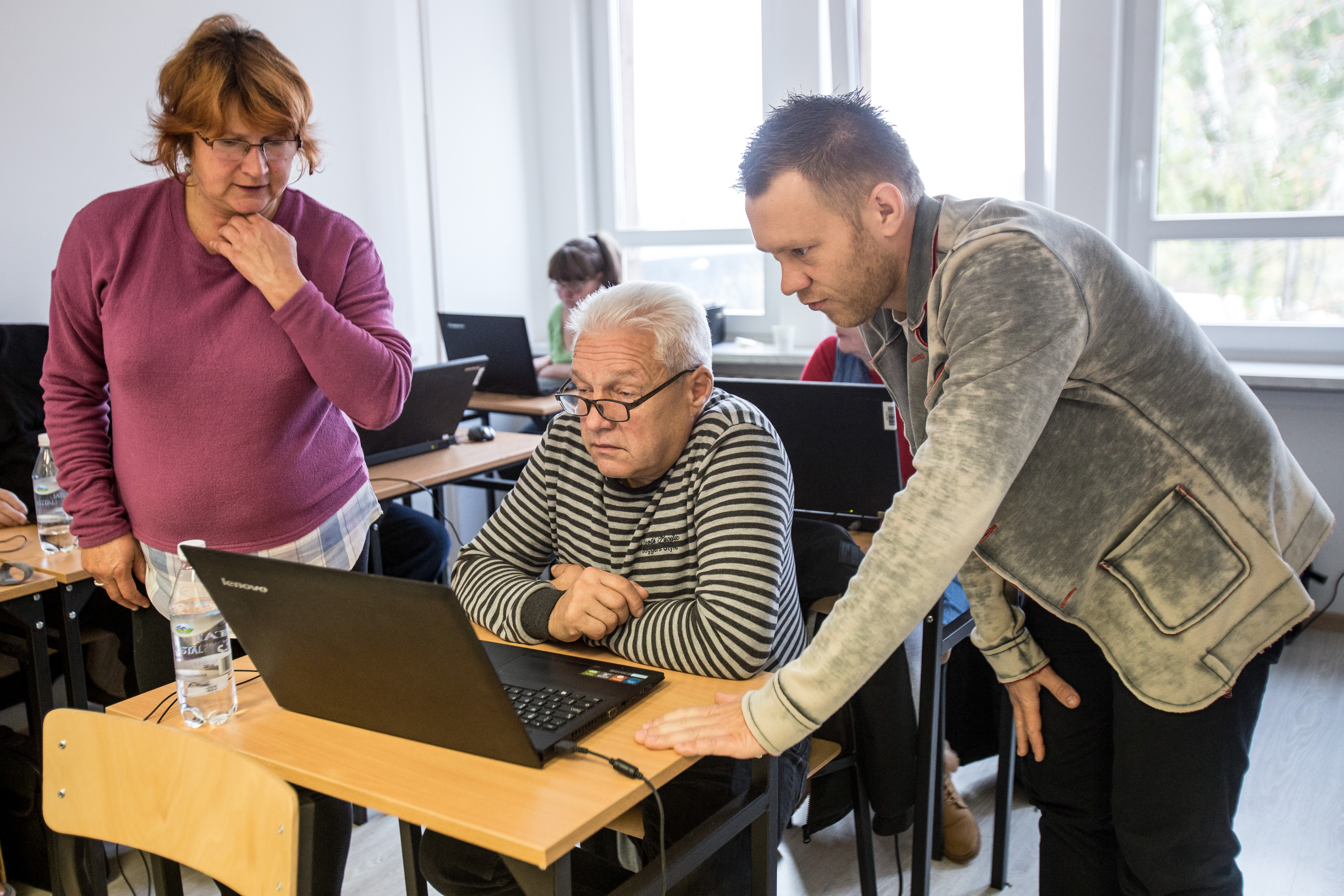 An elderly man sitting in front of a laptop during a computer course listening to the trainer's instructions.