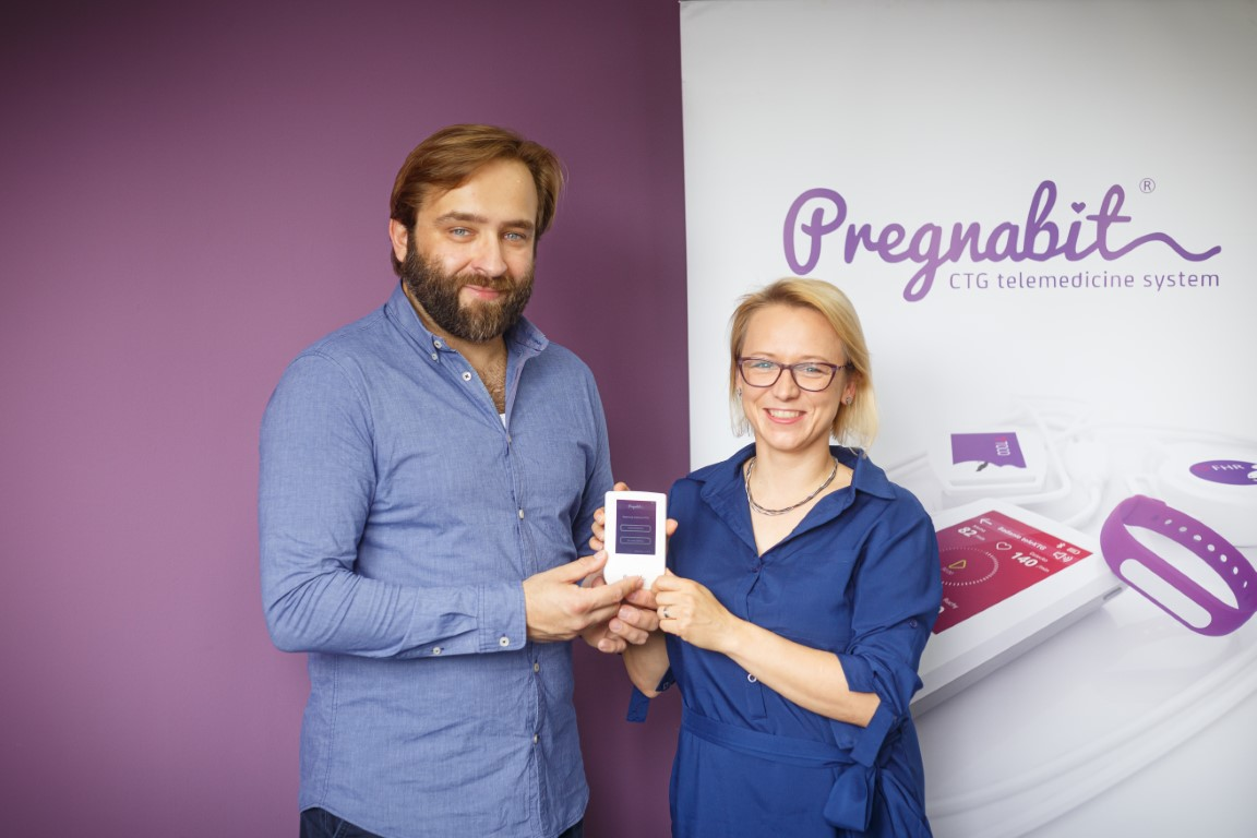 Man and women with a small mobile CTG apparatus (Pregnabit) in hands.