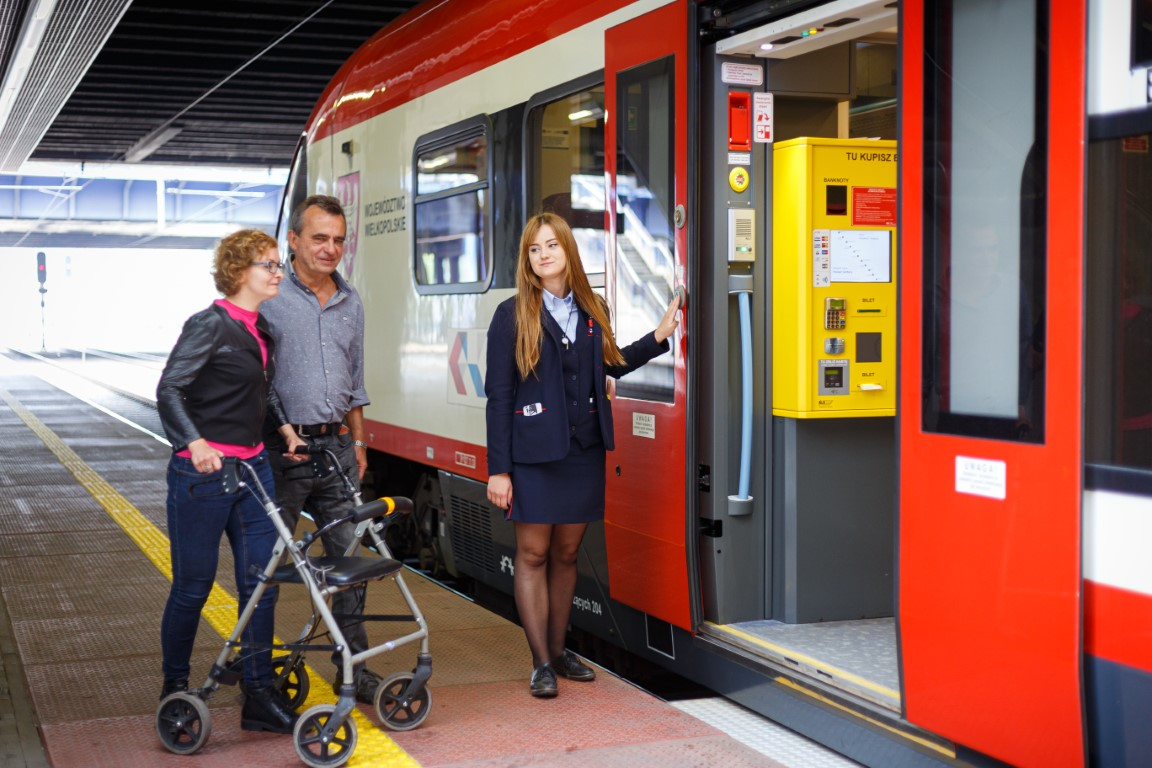 A woman with a walker close to a train with man and woman waiting for a ramp to be used.