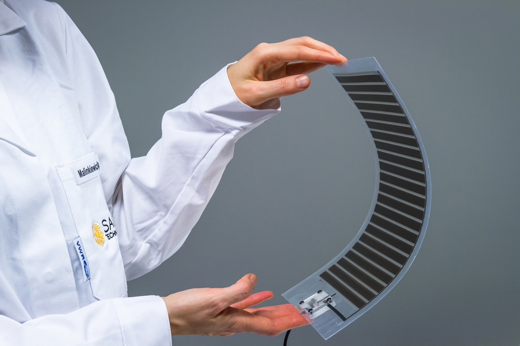 Hands holding flexible, printed perovskite solar cells.