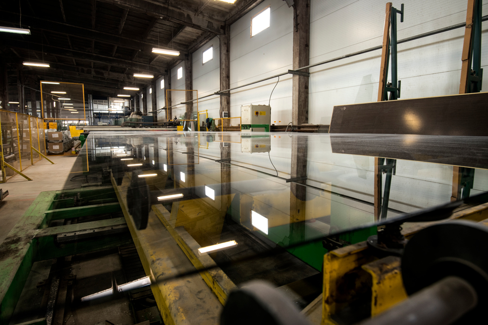 The photo presents a machine for the production of glass panes planted in the windows.