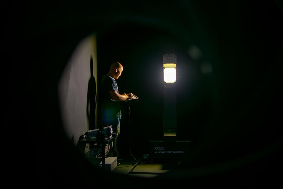 Mężczyzna prowadzi badanie oprawy oświetleniowej w ciemni fotometrycznej