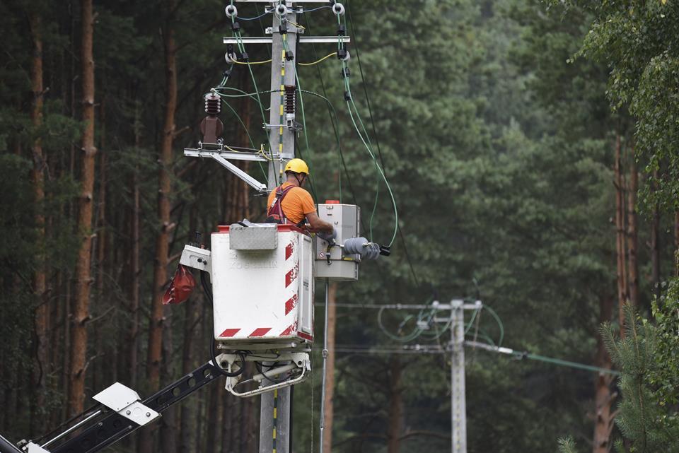 mężczyzna naprawia sieć wysokiego napięcia