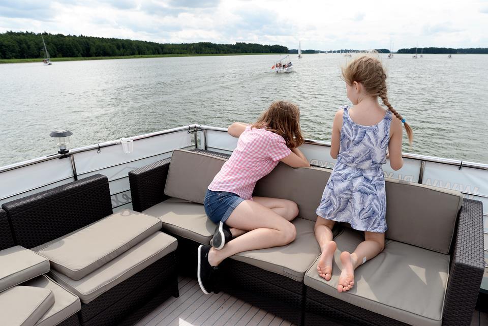 dwie dziewczynki siedzą tyłem na houseboacie