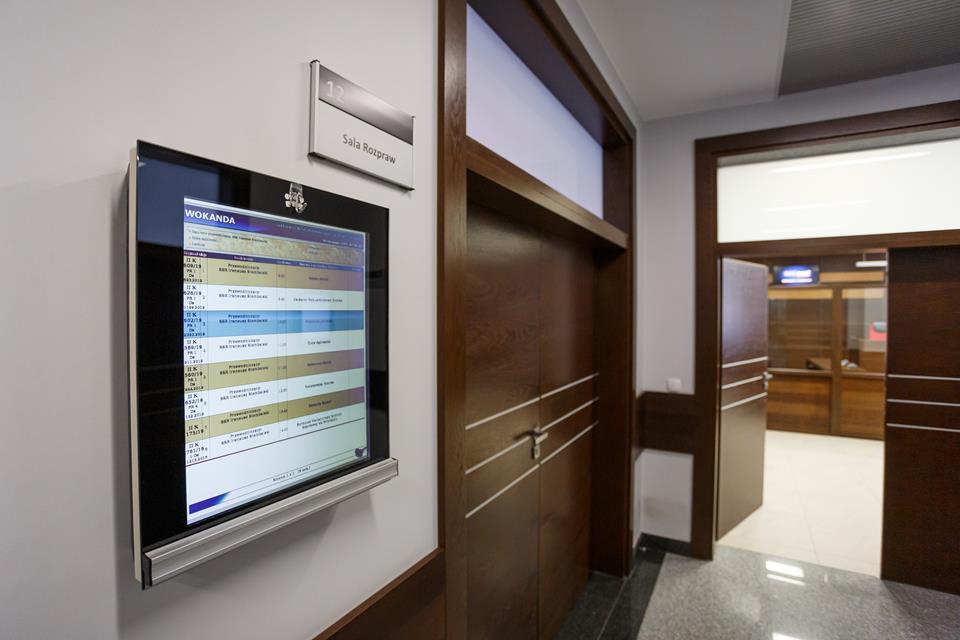 na ścianie sali rozpraw ekran z wyświetlającą sie informacją o wokandzie
