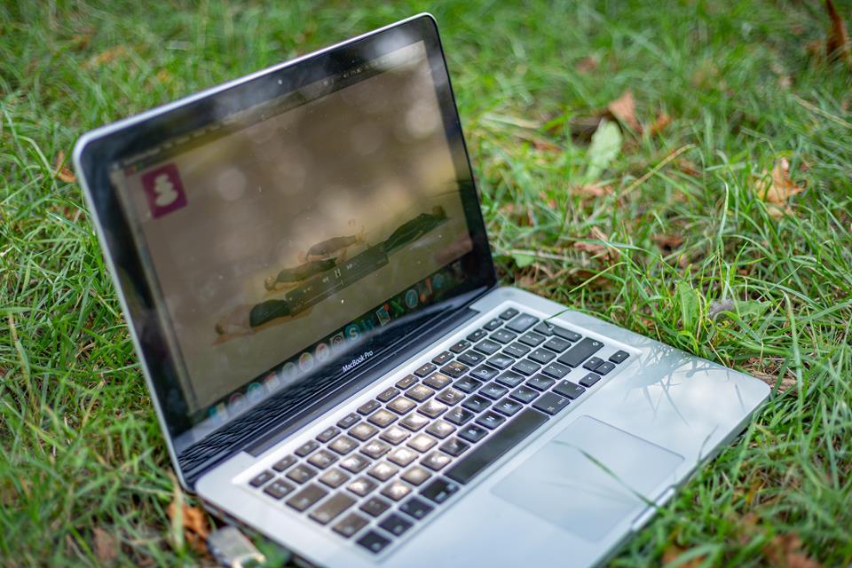 Laptop na trawie z wyświetlanym na ekranie poradnikiem wideo