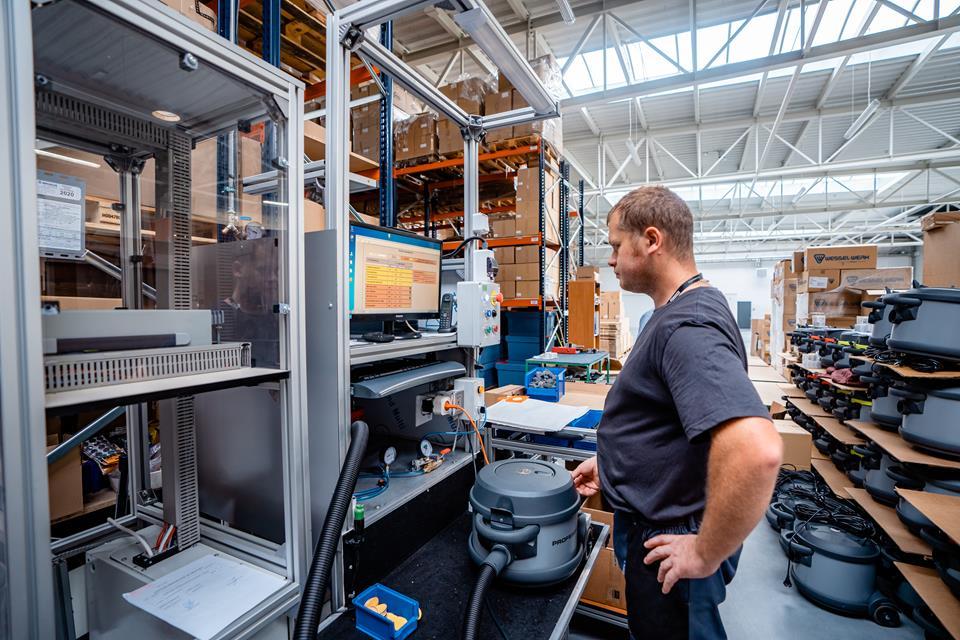 mężczyzna stoi przy maszynie w fabryce odkurzaczy