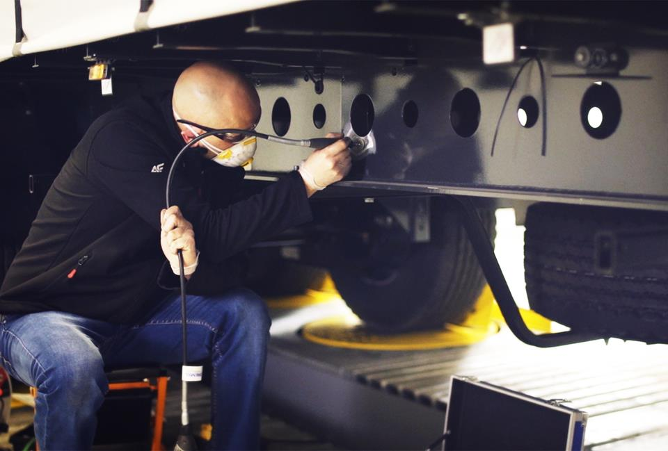 Mężczyzna przygotowuje konstrukcję podwozia naczepy do badań