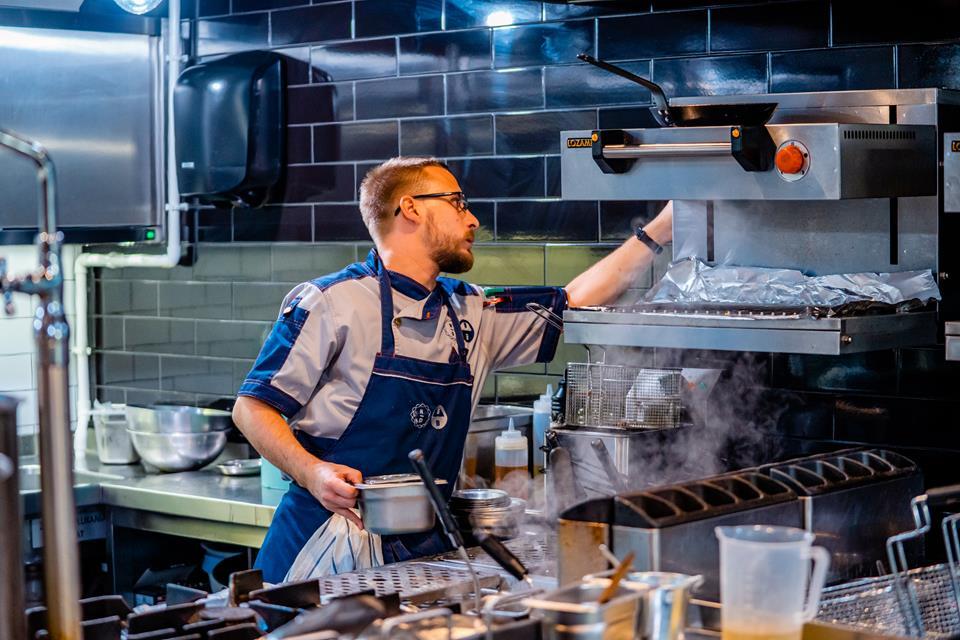 Kucharz przygotowuje dania w restauracyjnej kuchni